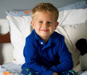 Boy Smiling on Bed