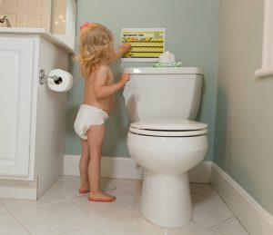 Girl putting sticker on potty training chart