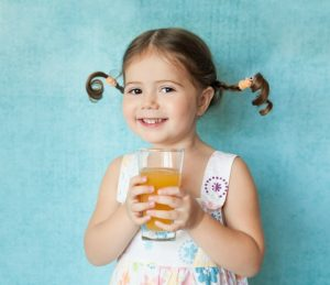 Girl Holding Glass of Orange Juice